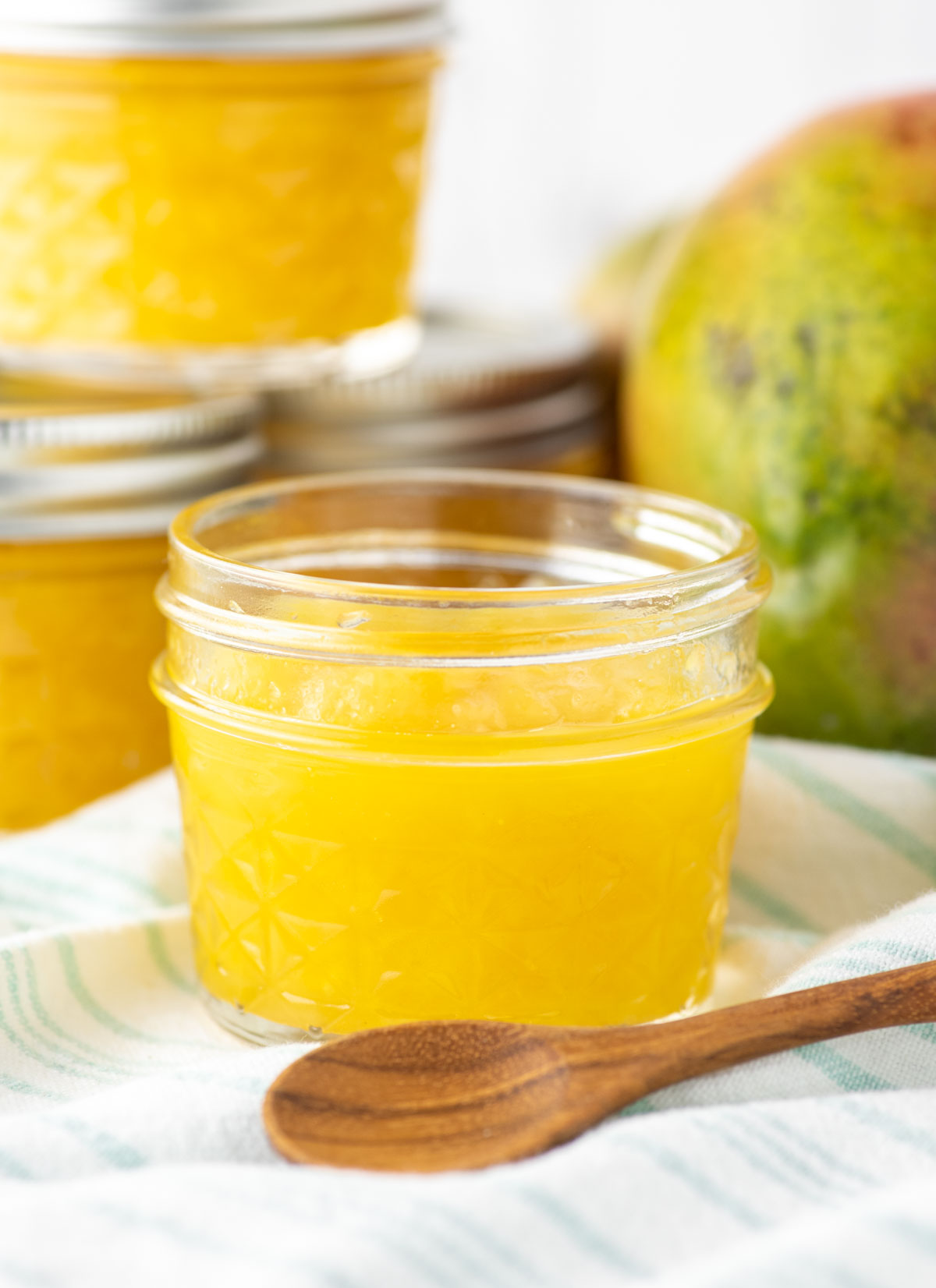 mango jam in glass jar with more jars in background