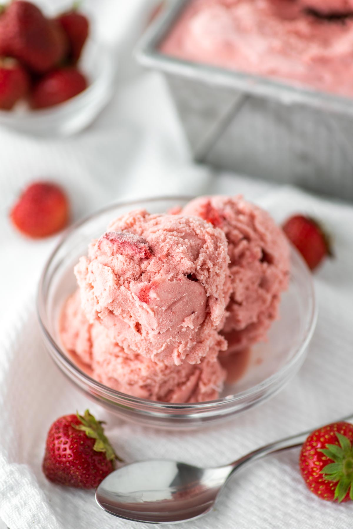 strawberry ice cream in glass bowl with container in background