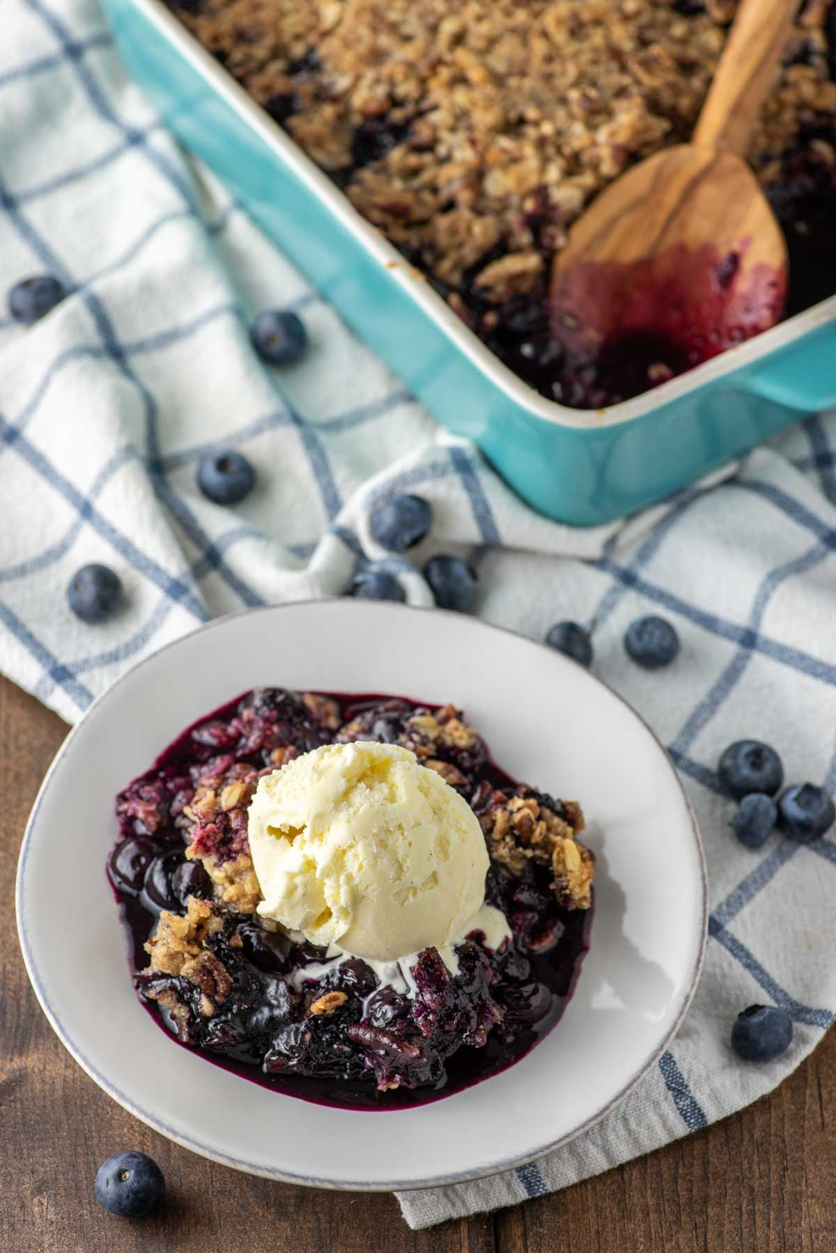 blueberry crisp on plate with baking dish in background