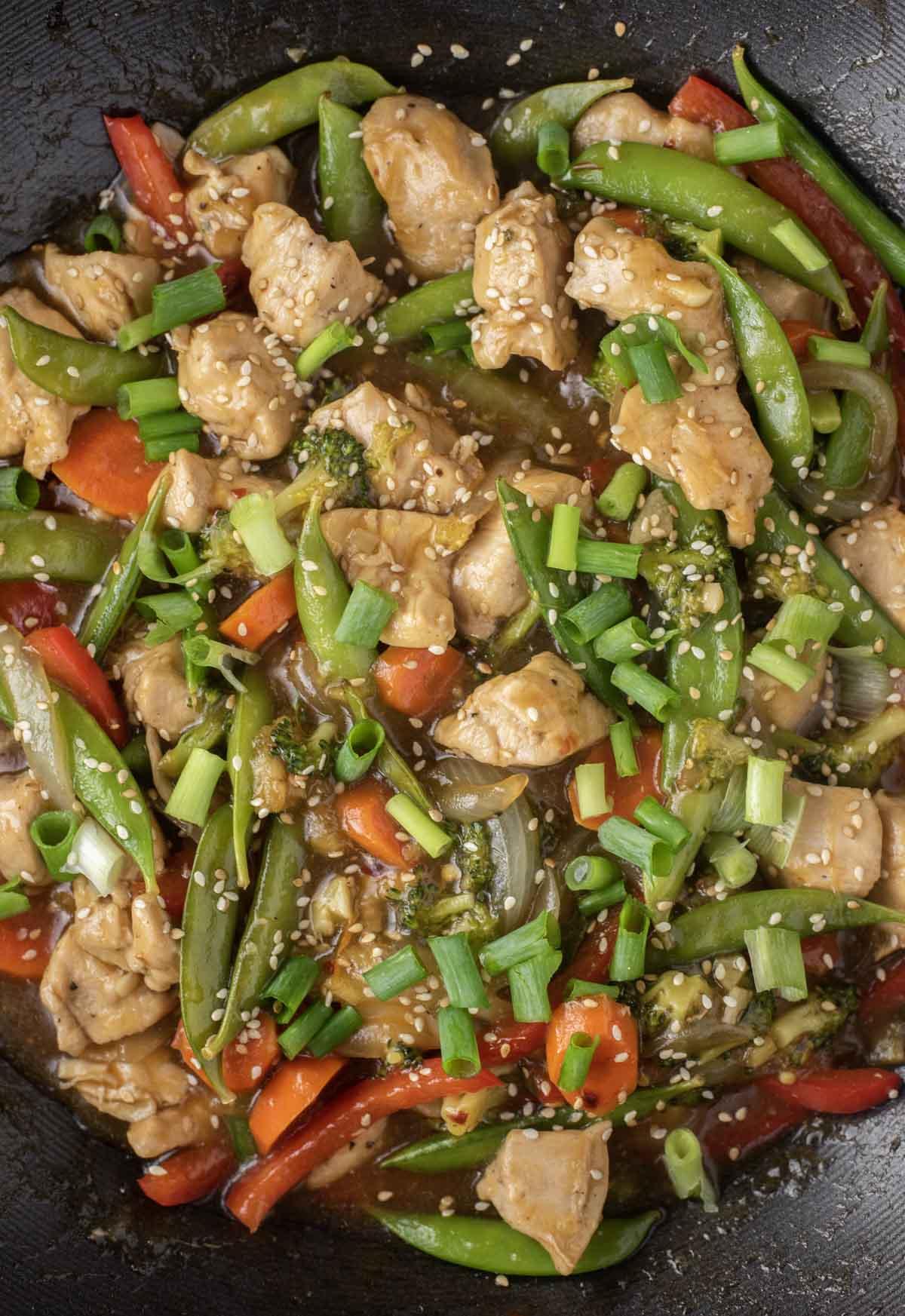 overhead shot of chicken and veggie stir fry in wok
