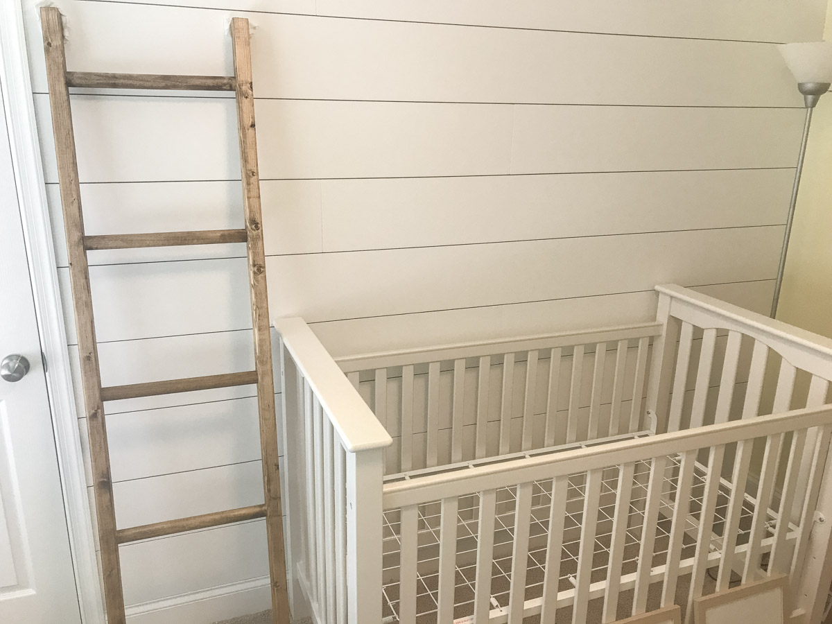 blanket ladder against shiplap wall with crib