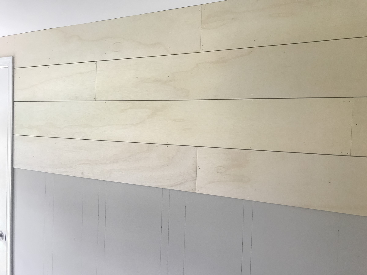 using spacers to nail DIY shiplap on wall