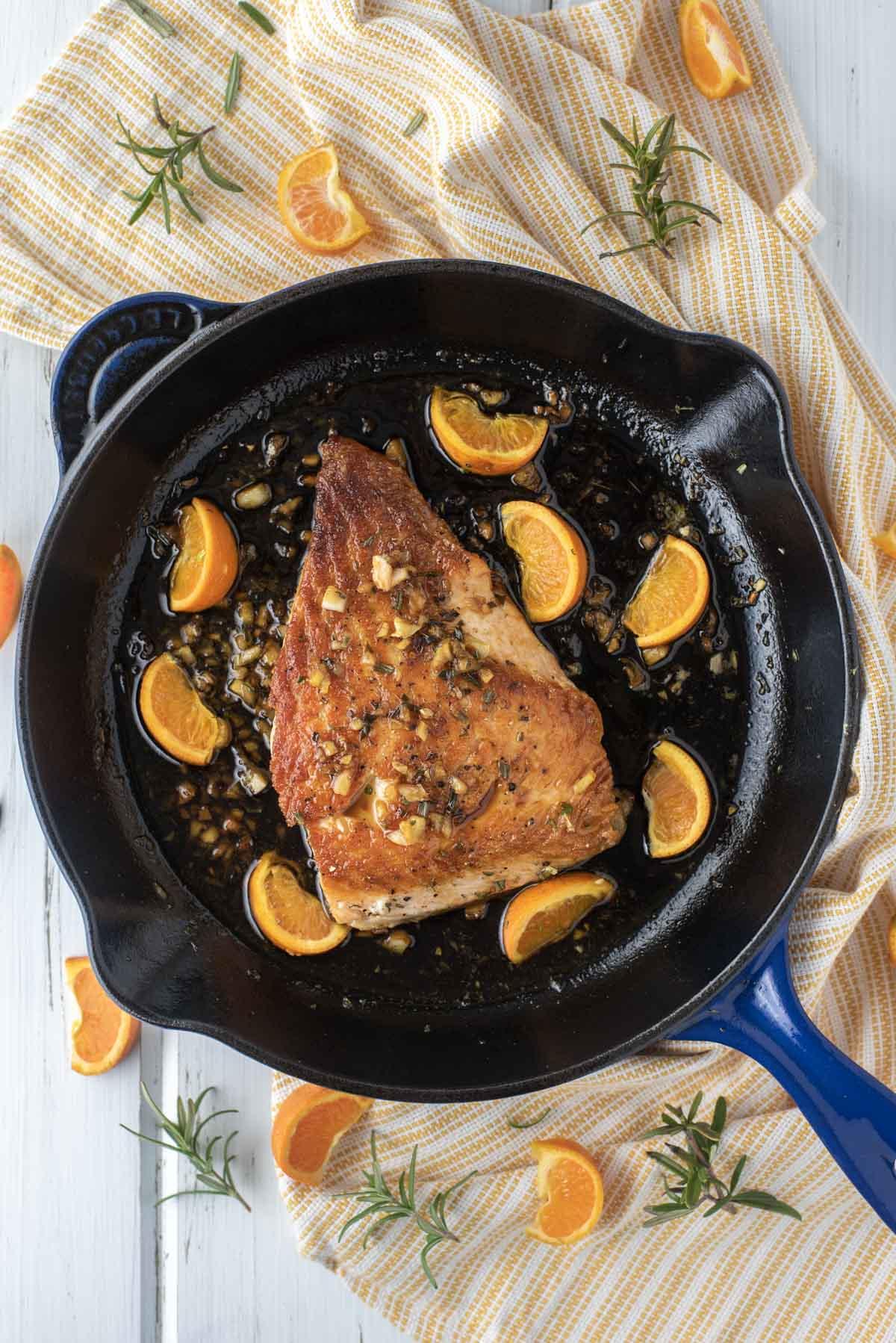overhead shot of orange glazed salmon in cast iron skillet on dish towel
