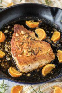 orange glazed salmon in cast iron skillet