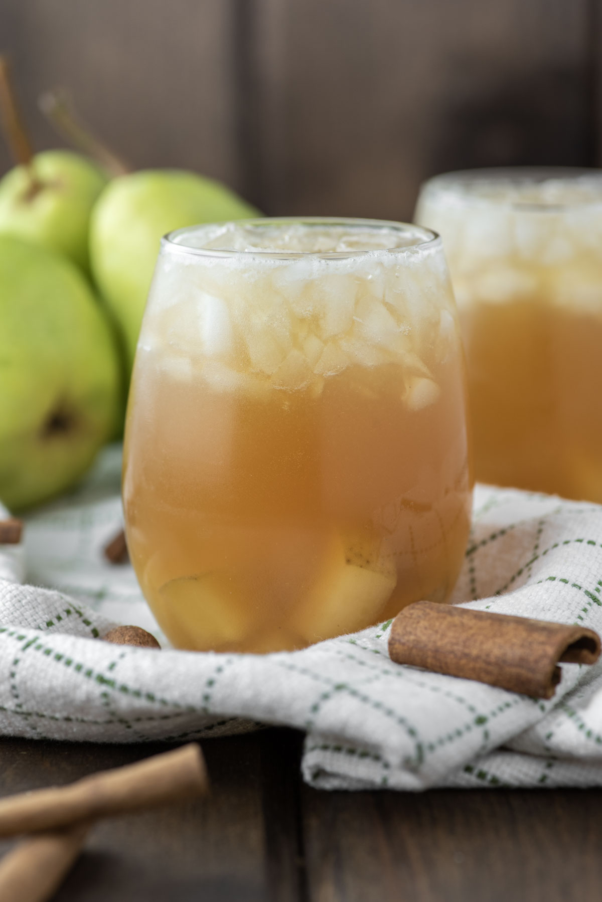 two pear cocktails in glasses on dish towel