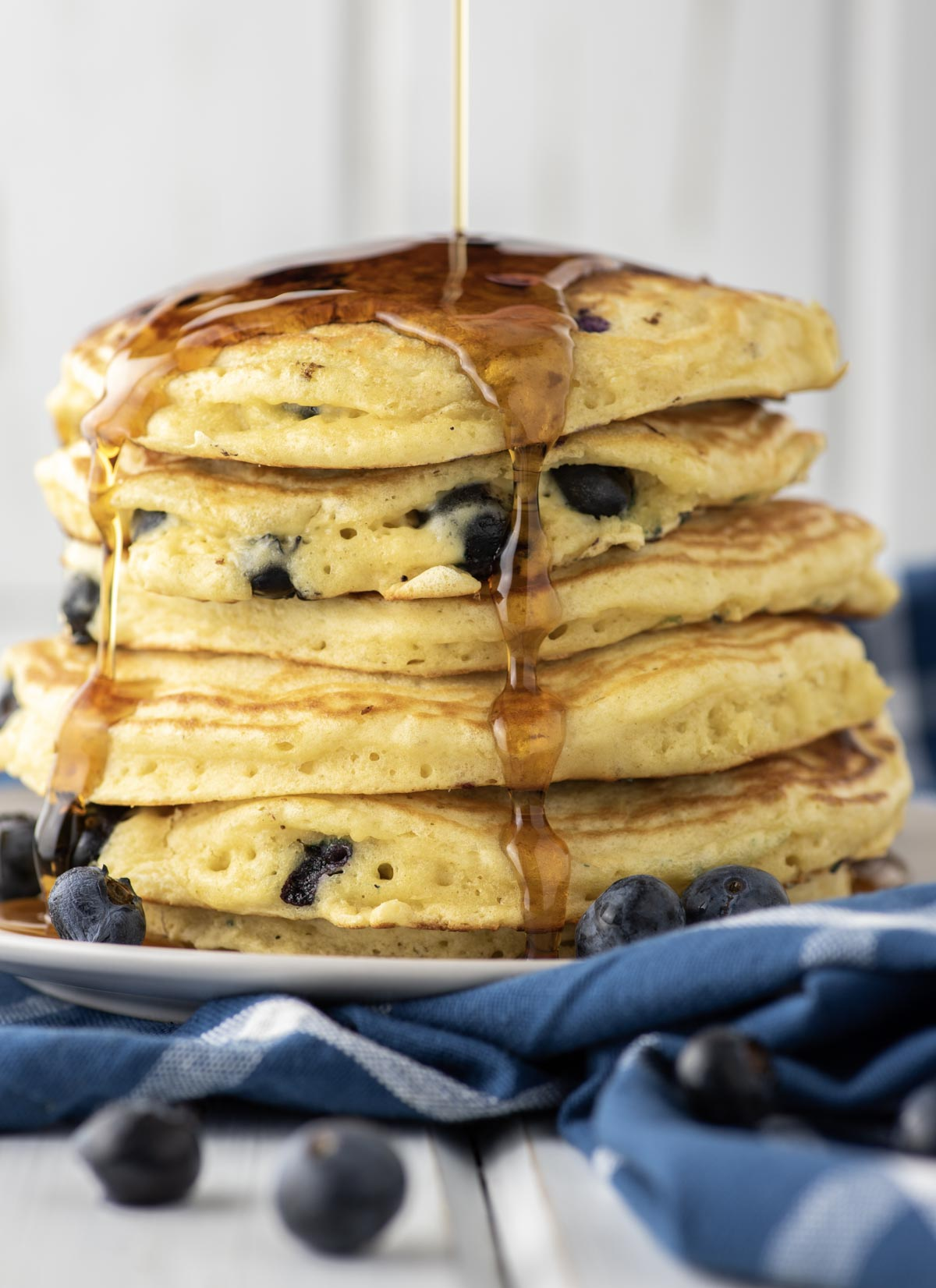 maple syrup being drizzled over stacked blueberry pancakes