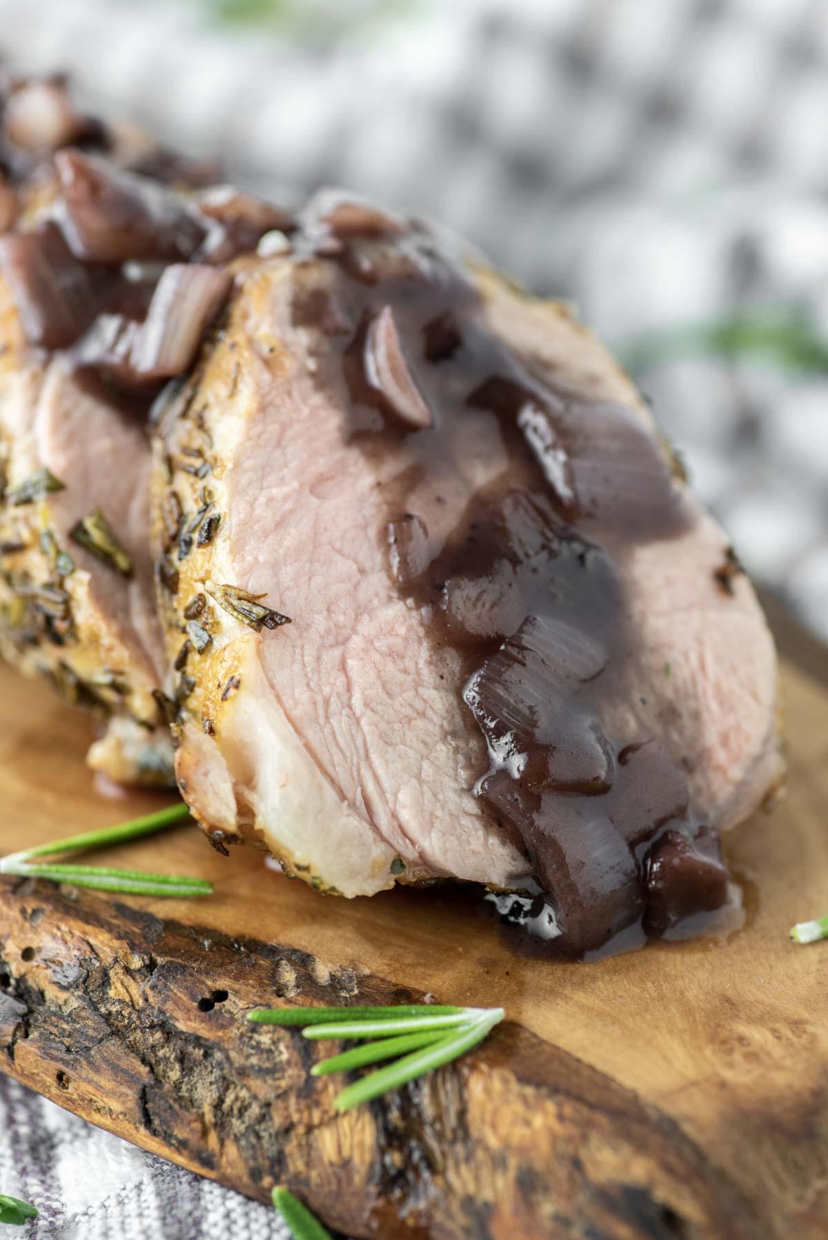 sliced pork tenderloin on wood board with red wine sauce