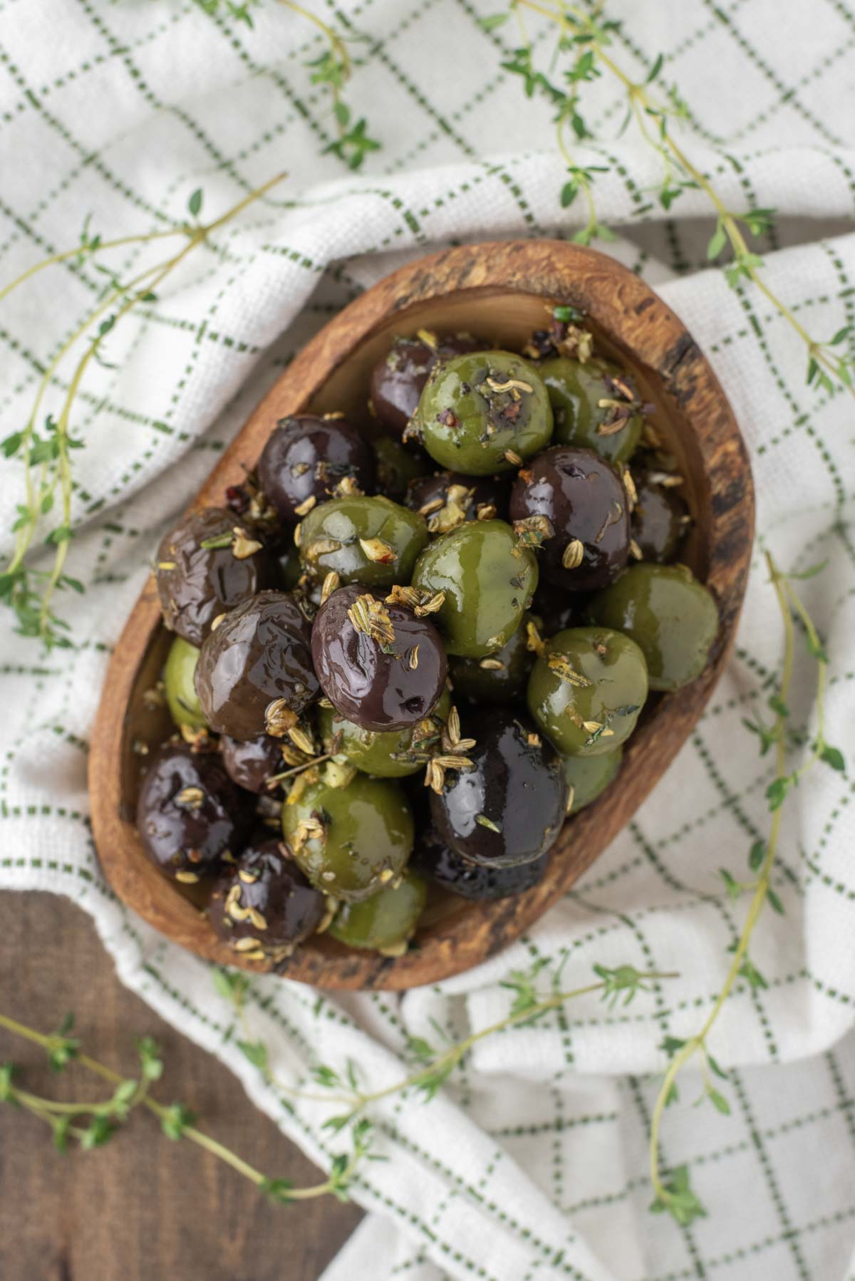overhead shot of marinated olives in wood bowl