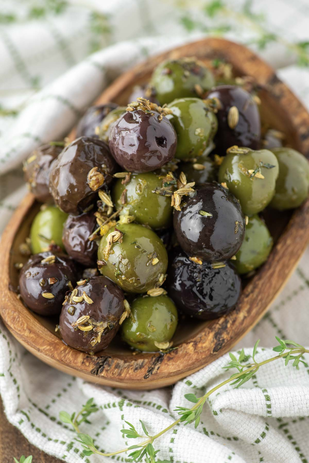 marinated olives in wood bowl on dish towel