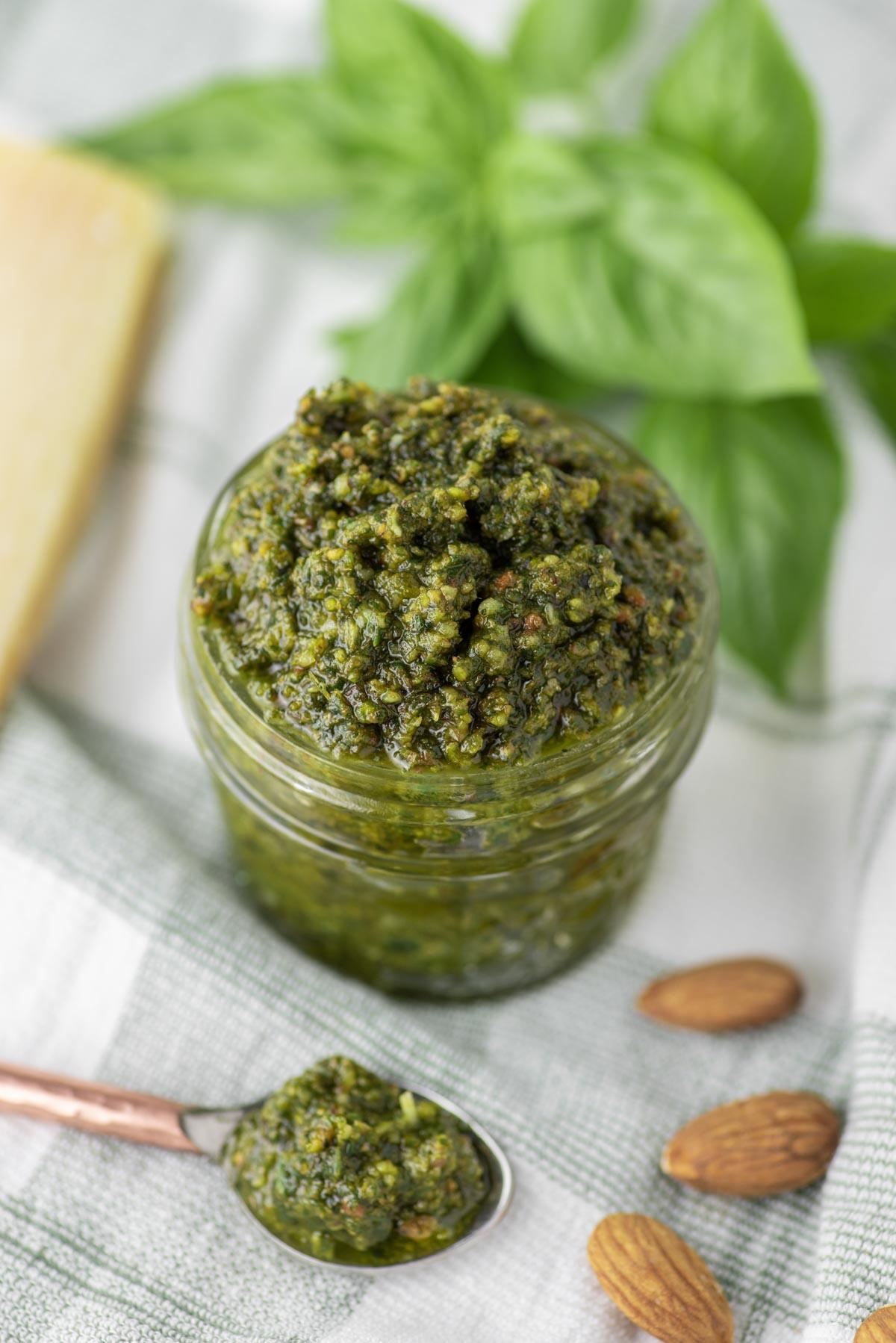 almond basil pesto in glass jar on dish towel
