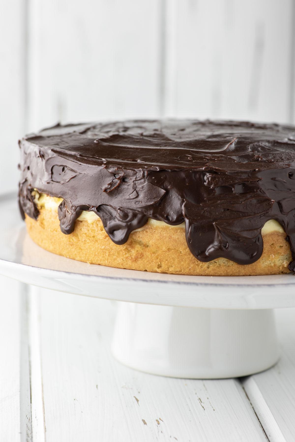 cake with cream and chocolate ganache on white plate