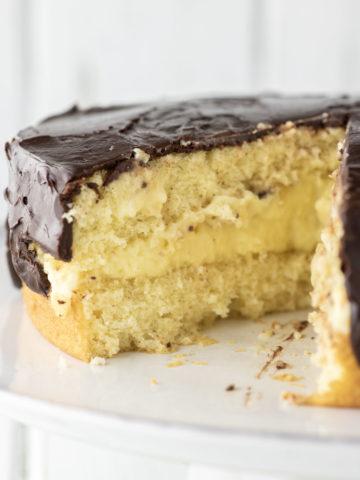 sliced Boston cream pie on white cake stand