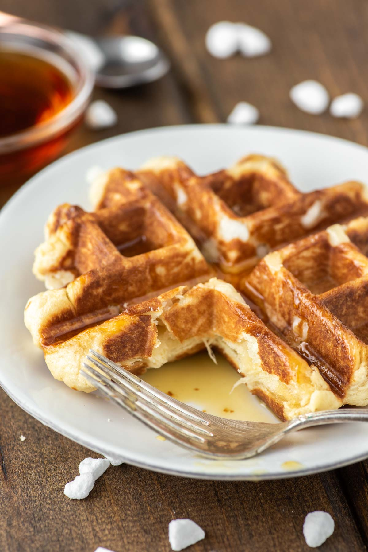 fork cut through waffle on white plate
