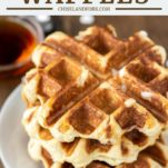 3 Liège waffles stacked on white plate with maple syrup in background