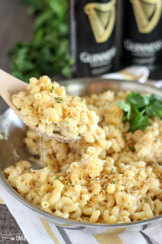 Guinness and Irish cheddar mac and cheese being lifted out of bowl with wooden spoon