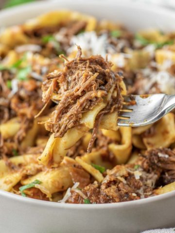 spoon lifting out pasta with meat from bowl