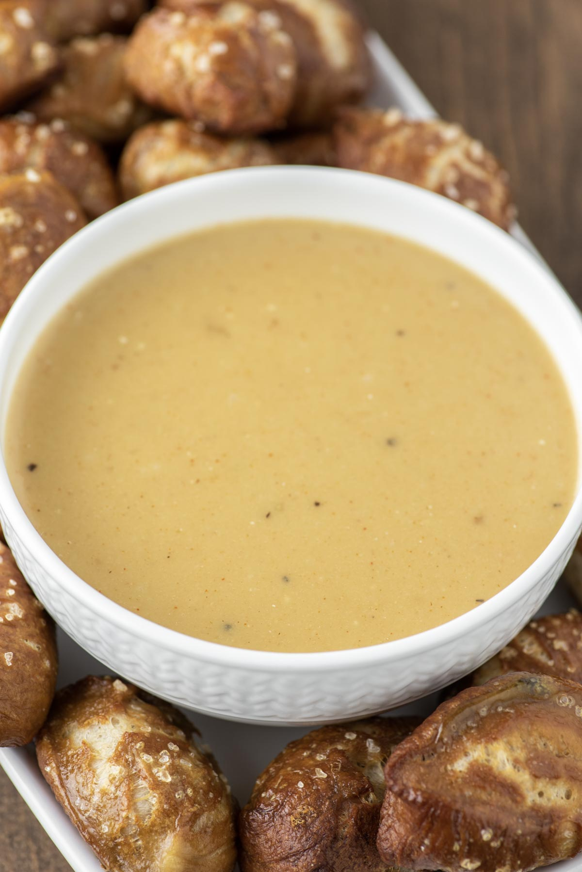 beer cheese dip in white bowl with pretzel bites