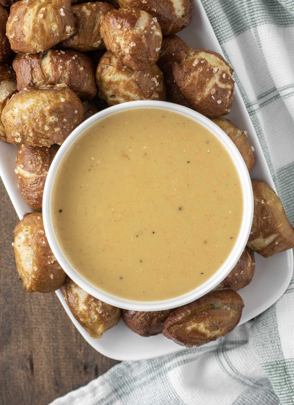 overhead shot of beer cheese dip in white bowl with pretzel bites
