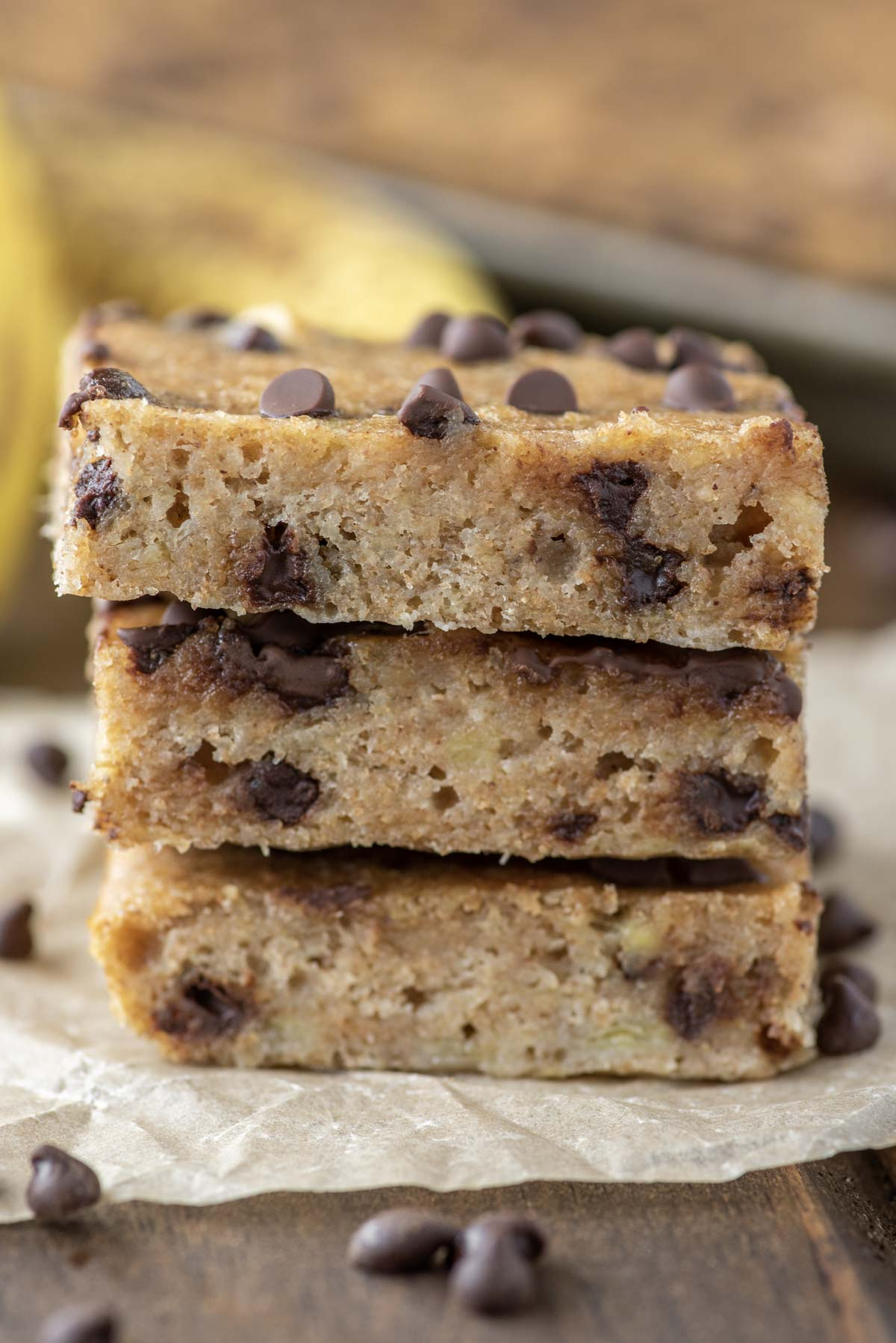 3 stacked chocolate chip banana bars on parchment paper