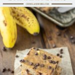 3 banana bars on parchment paper with baking sheet and bananas in background