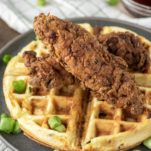 two pieces of fried chicken on bacon cheddar waffle