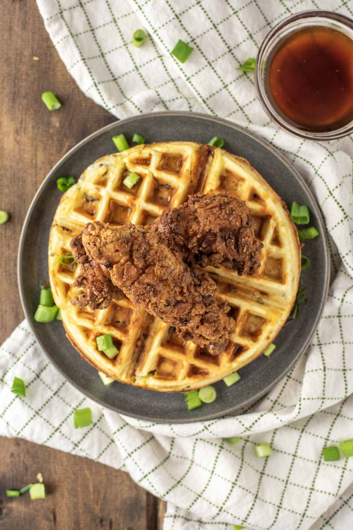 overhead shot of fried chicken and waffles on grey plate