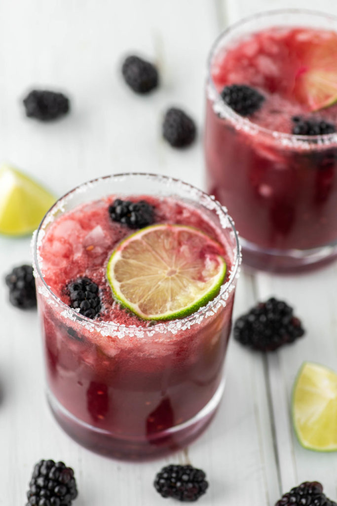 two blackberry margaritas in glasses on white board