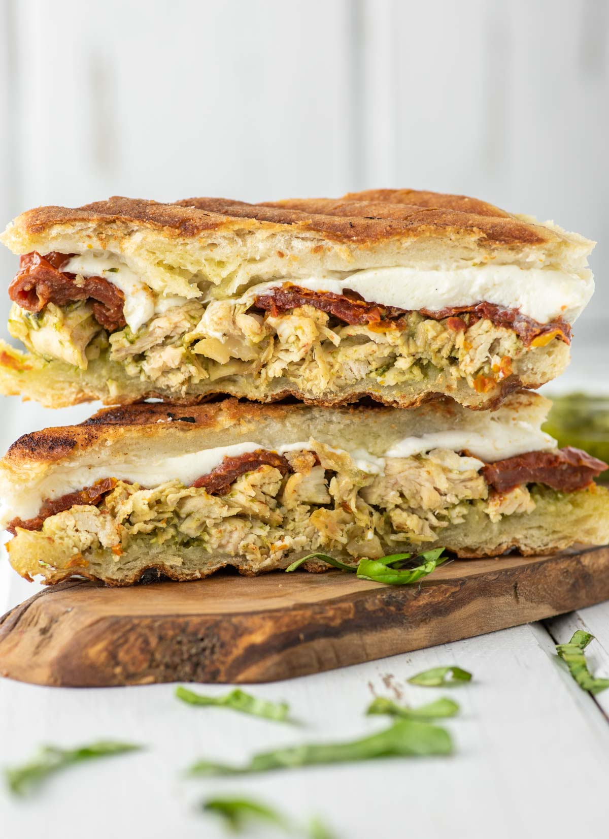 two slices of chicken pesto panini on wood board