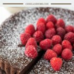 slice of flourless chocolate cake with raspberries being pulled away