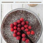 overhead shot of flourless chocolate cake with raspberries on white plate