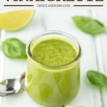 basil lime vinaigrette in glass jar with basil on white board