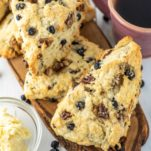 blueberry scones on wood board with cup of coffee