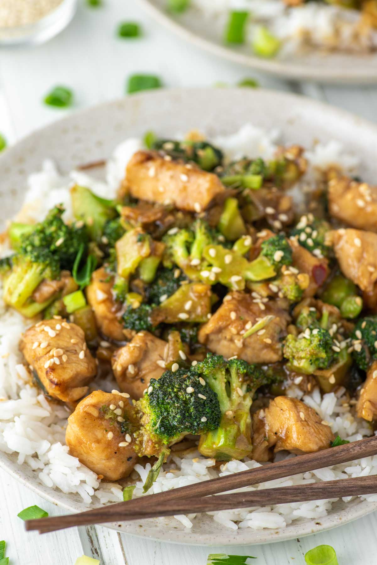 close-up of chicken and broccoli stir fry with rice on speckled plate