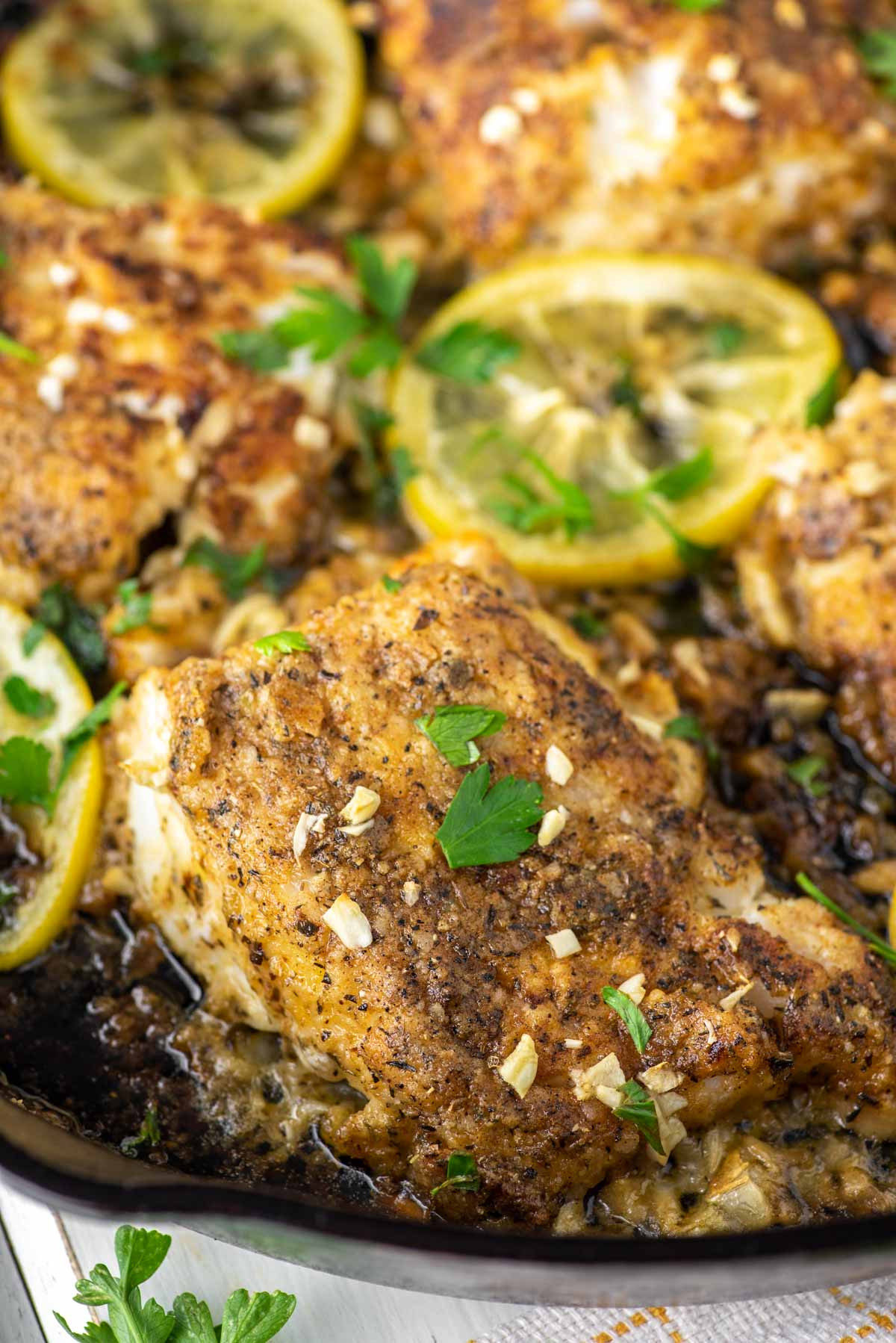 close-up of baked cod with lemons in skillet