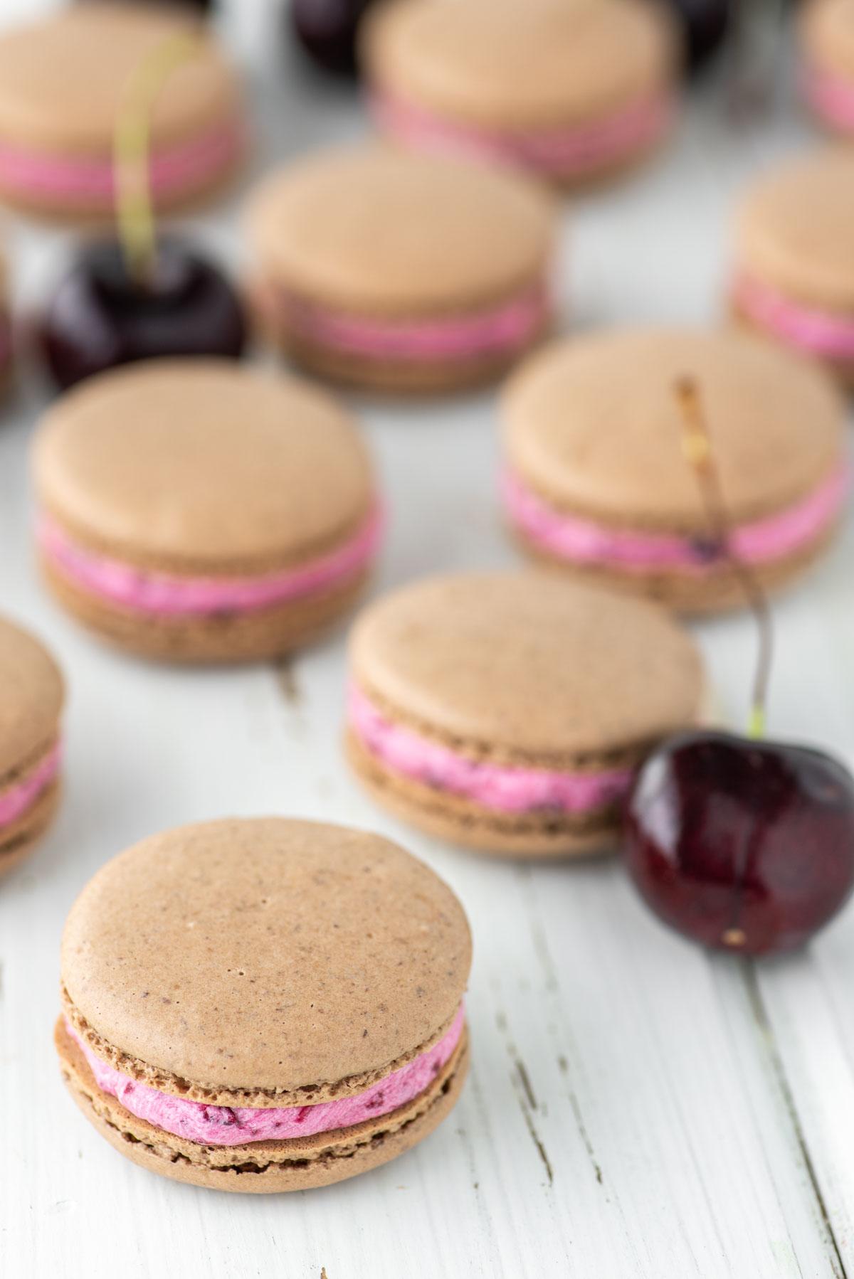 chocolate cherry macarons on white board