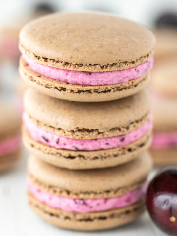 3 stacked cherry macarons with more in the background