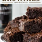 Guinness brownies stacked on white plate with beer bottle in background