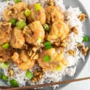 overhead shot of honey walnut shrimp over rice on grey plate