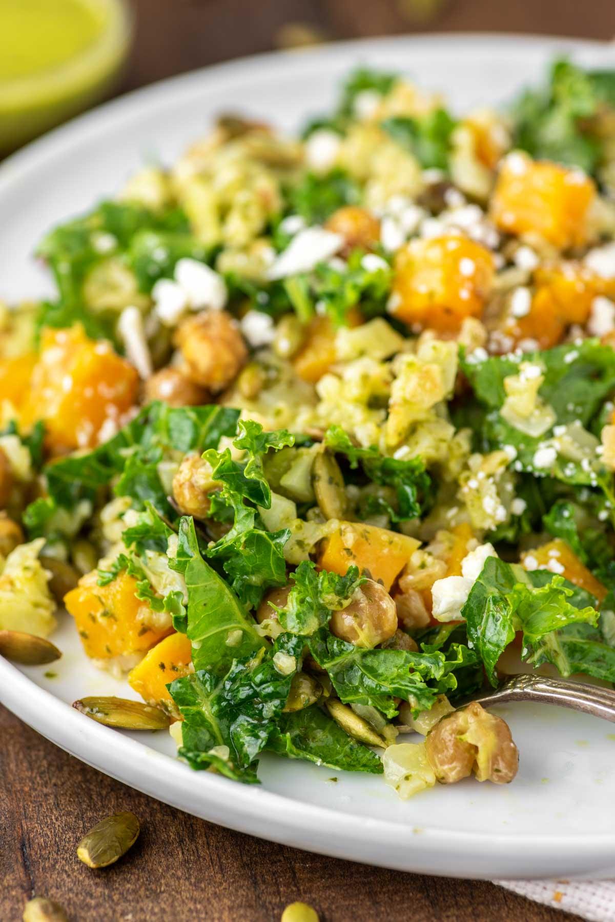 fork in kale cauliflower salad on white plate
