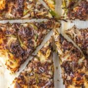 overhead shot of cheesesteak pizza on parchment paper