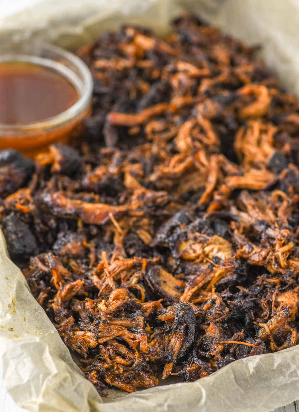 oven roasted pulled pork in pan lined with parchment paper with glass bowl of bbq sauce