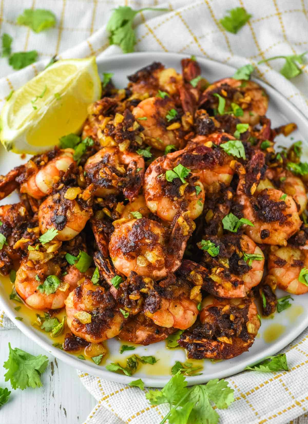 Hawaiian garlic shrimp stacked on white plate