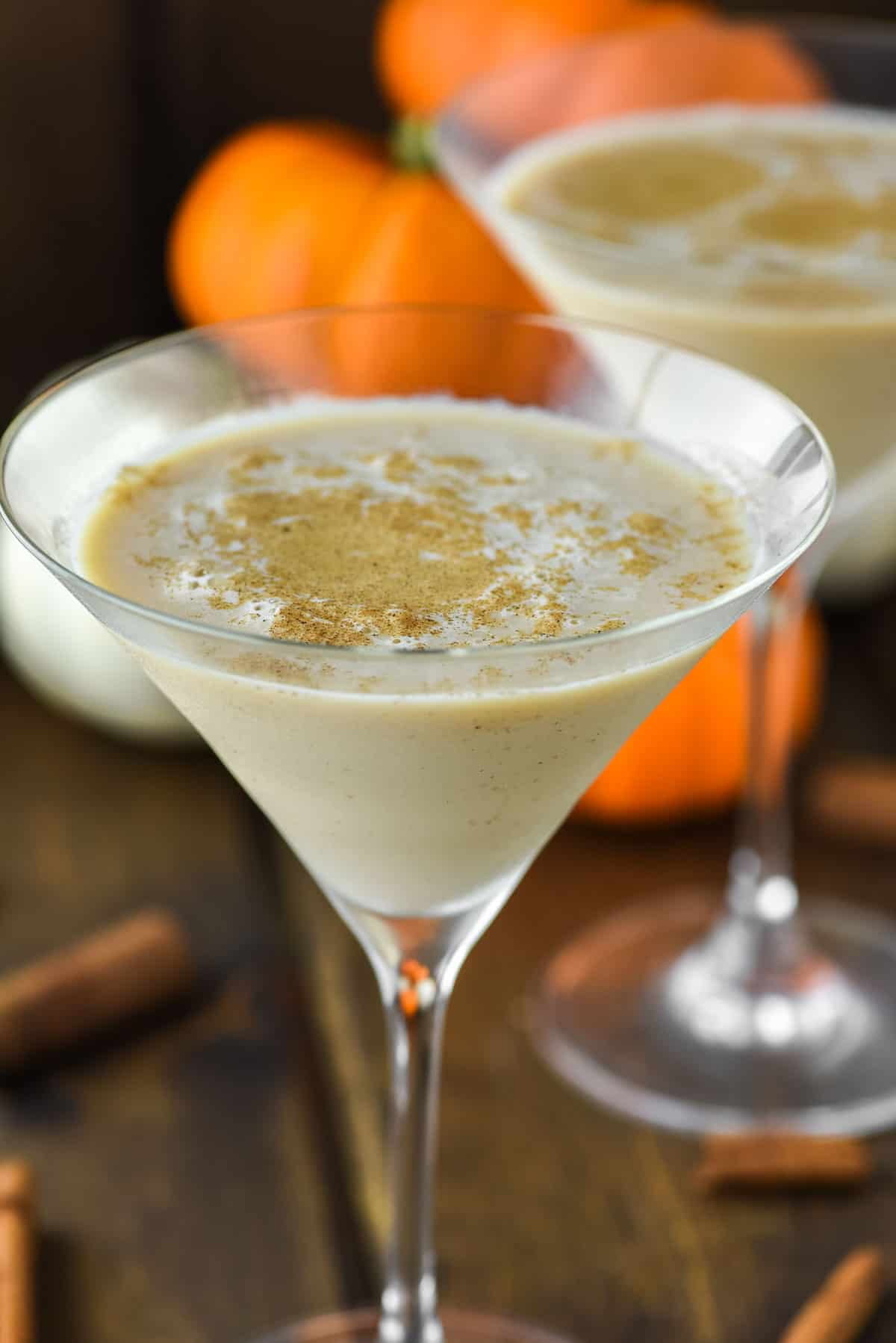 two glasses of pumpkin spice martinis with pumpkins in the background