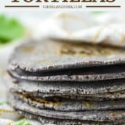 stacked homemade blue corn tortillas wrapped in dish towel