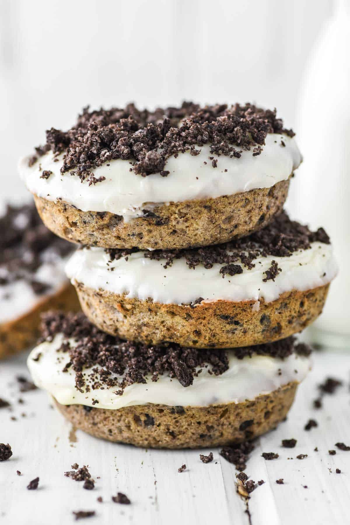 3 stacked Oreo donuts with glass of milk in background