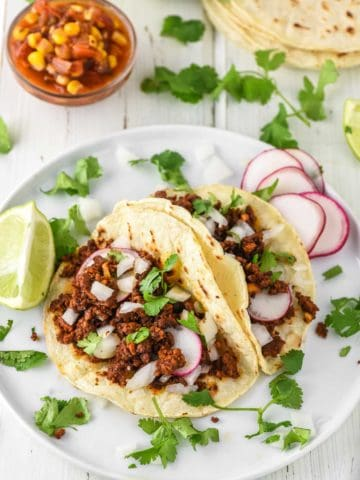 two tacos with homemade chorizo on white plate