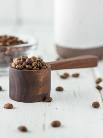 handmade coffee scoop with coffee beans on white board with bowl of coffee beans and mug in background