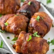 bacon wrapped chicken thighs on white plate