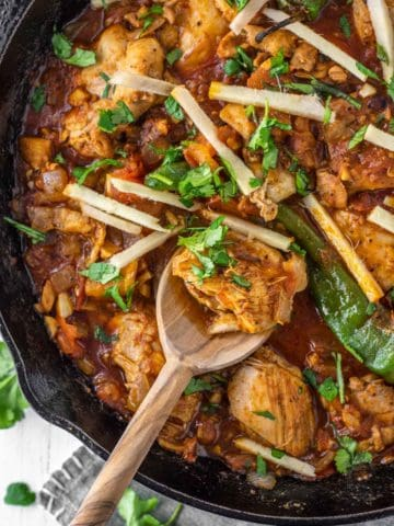 overhead shot of spoon dipped in kadai chicken in cast iron skillet