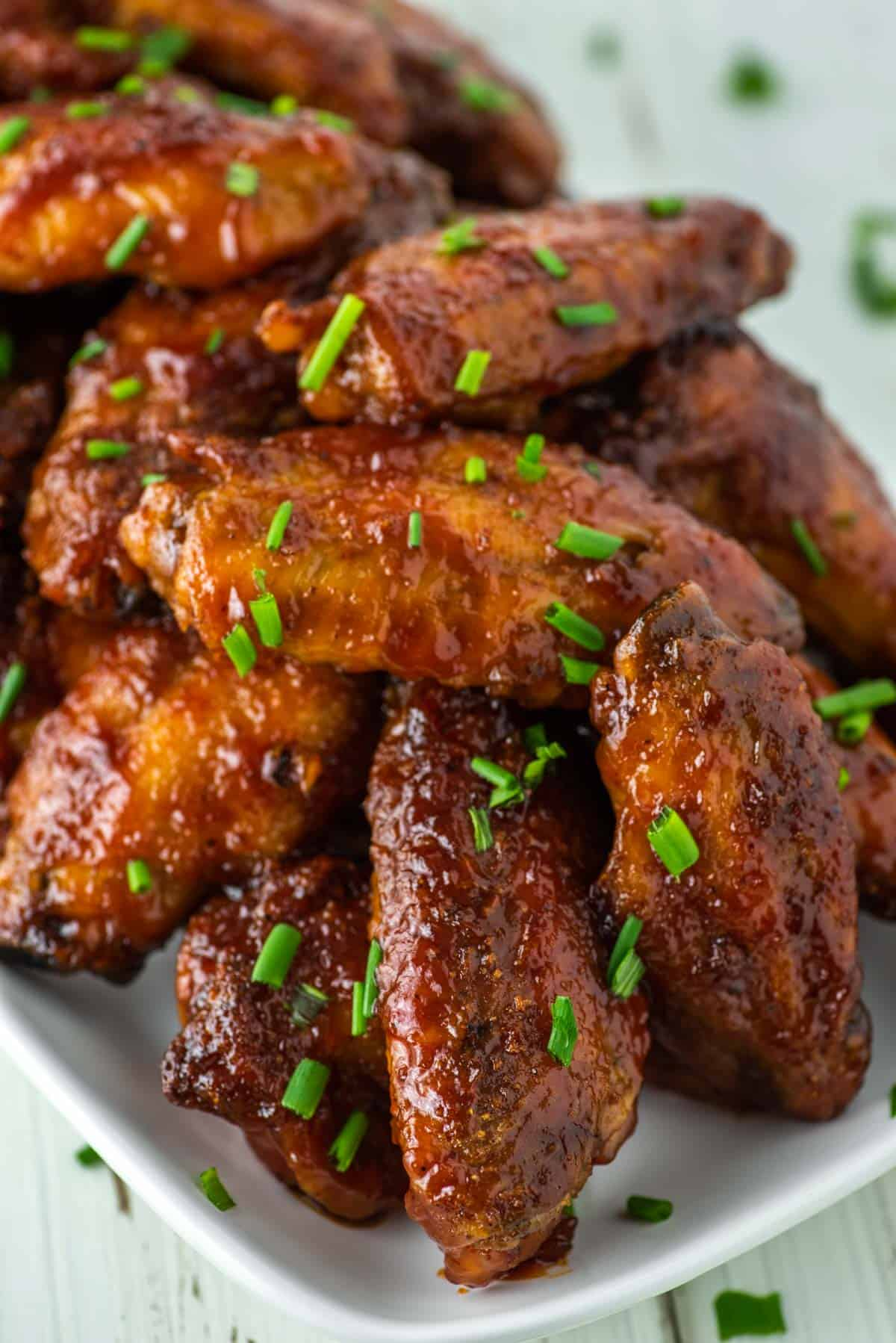 close-up of stacked honey bbq wings on plate